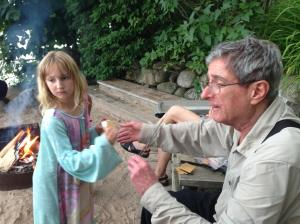 Lily geting a s'more assist from her Grandpa Grekin in the summer of 2014